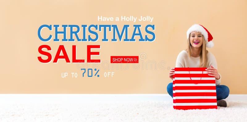Message de vente de Noël avec la femme avec le chapeau de Santa tenant un sac à provisions photo stock