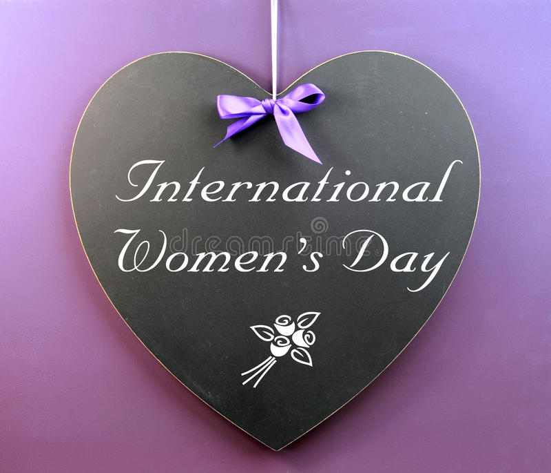 Message du jour des femmes internationales écrit sur le tableau noir de forme de coeur photo stock