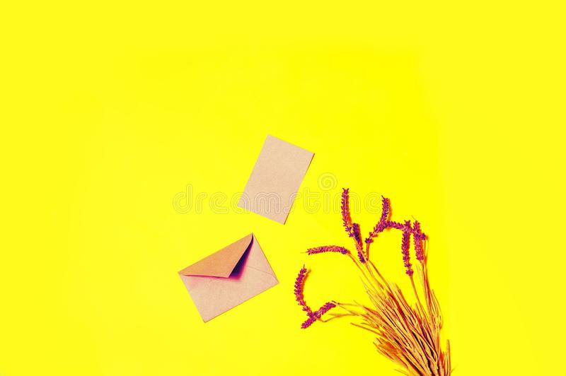 Message in envelop. Top view opened pink envelop and lavender flowers on yellow background stock images