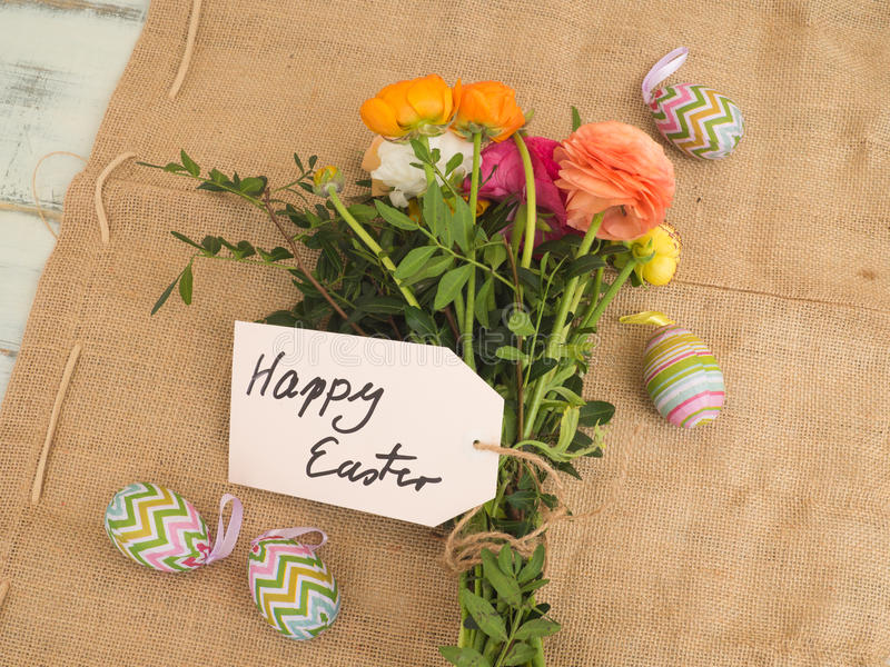 Message happy easter on fabrics with a bouchet of flowers. And some easter eggs from the top stock photography
