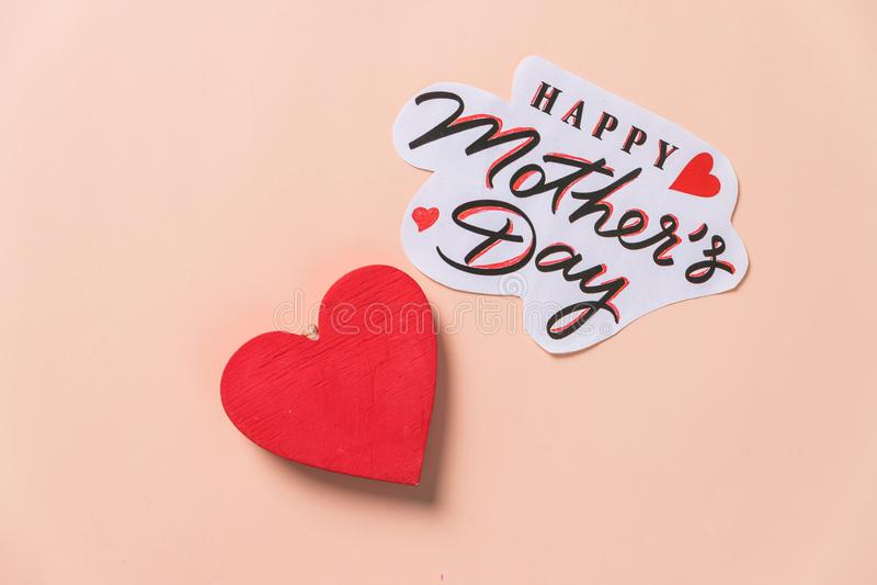 Message heureux du jour de mère avec le coeur en bois rouge sur le fond en pastel carte postale de f?te Concept d'amour pour le j photographie stock
