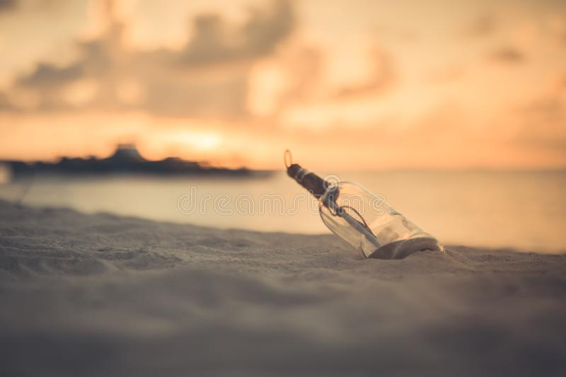 Message with letter inside the bottle on a beach in sunset stock image