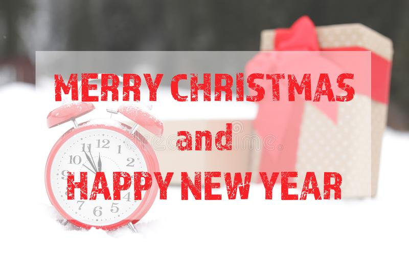 Message MERRY CHRISTMAS AND HAPPY NEW YEAR with red alarm clock and gift boxes on snow outdoors. stock photo