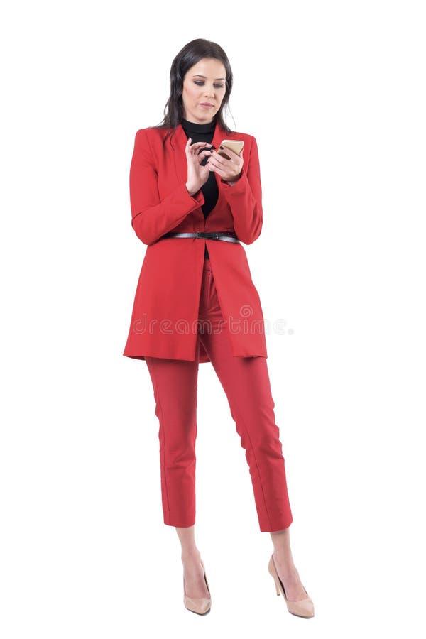 Message ou email de dactylographie occupé sérieux de femme d'affaires au téléphone portable photographie stock