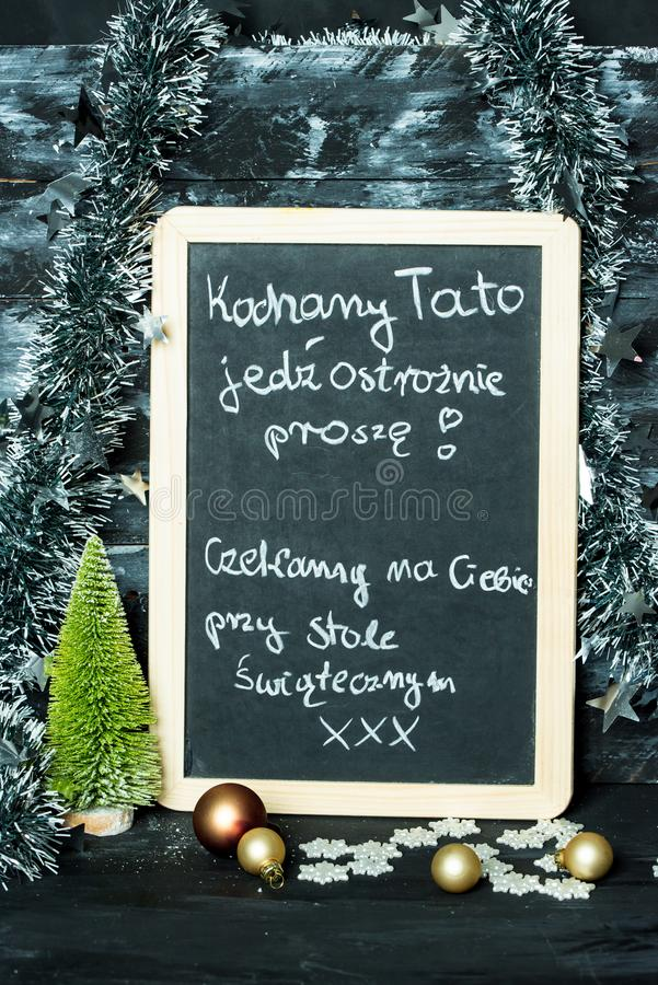 On a Christmas background a blackboard with a message from child to father: Drive carefully, we are waiting for you royalty free stock photo