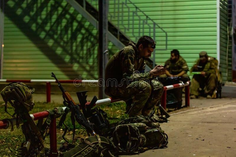 Message sérieux d'écriture de soldat de vue de côté dans le téléphone tout en portant dans l'uniforme et entouré par des armes te images stock