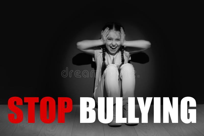 Message STOP BULLYING and crying little girl. Sitting on floor near dark wall, black-white effect stock photography