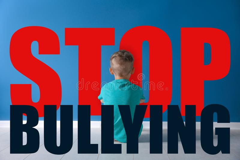 Message STOP BULLYING and sad little boy sitting. On floor near color wall stock photos