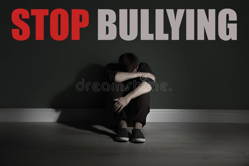 Message STOP BULLYING and sad young man. Sitting on floor near color wall stock photo