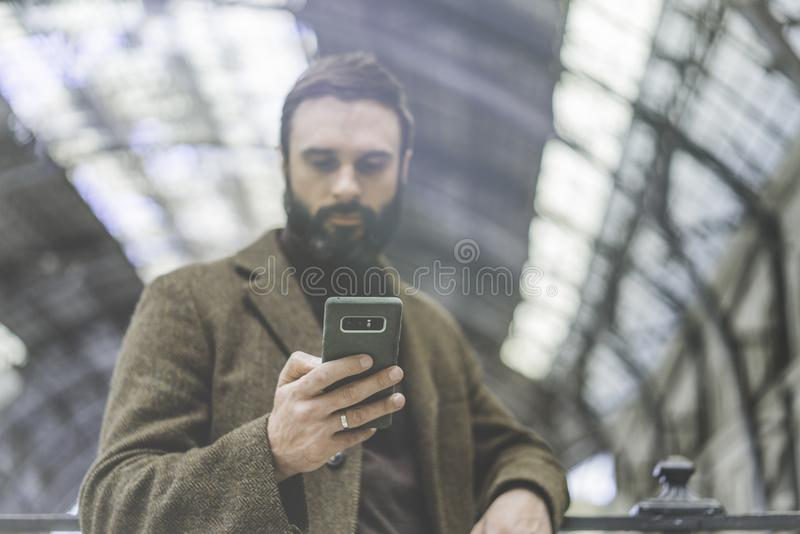 Message textuel attrayant d'homme d'affaires à son téléphone portable Entrepreneur professionnel occasionnel à l'aide du smartpho photos libres de droits