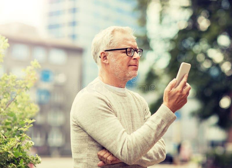 Message textuel d'homme sup?rieur sur le smartphone dans la ville images stock