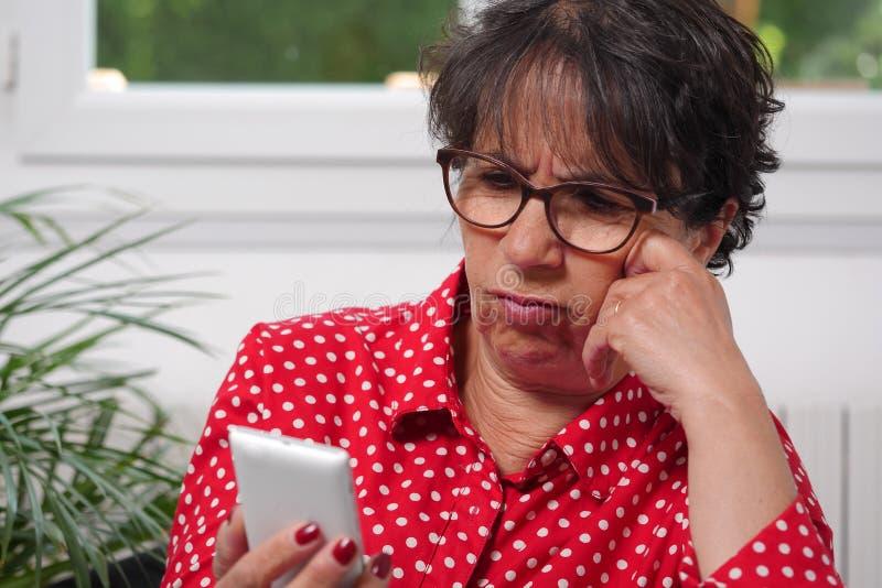 Message textuel d'une cinquantaine d'années de lecture de femme à son téléphone portable image stock