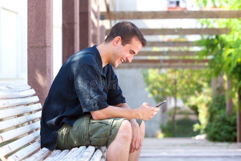 Message textuel de sourire de lecture d'homme au téléphone portable images stock