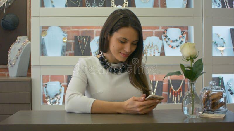 Message textuels femelles gentils de vendeur sur le smartphone et sourire mignon dans un magasin de bijoux image stock