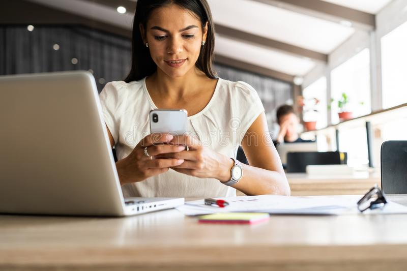 Message to business partner. Cheerful beautiful woman using her smartphone with smile at her working place. Message to business partner. Cheerful beautiful stock photo