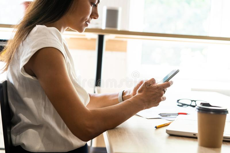 Message to business partner. Cheerful beautiful woman using her smartphone with smile at her working place. Message to business partner. Cheerful beautiful stock images