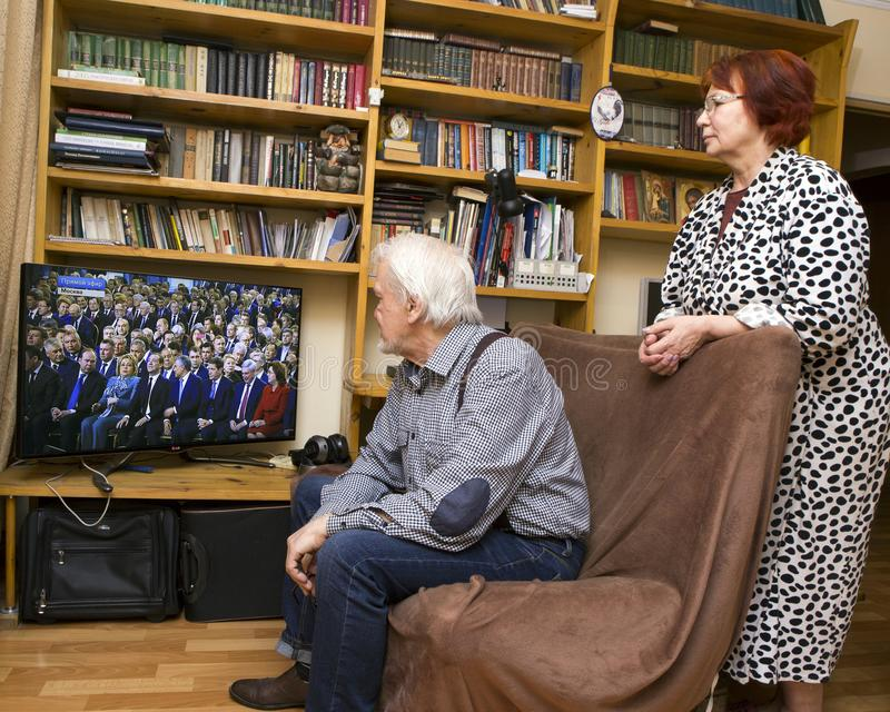 Message to the Parliament of the Russian President. ULAN - UDE, RUSSIA - February 20, 2019: a married couple of Russian pensioners at home are watching on TV the stock image