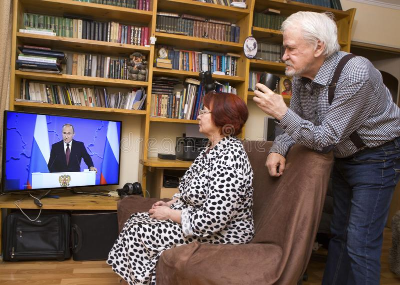 Message to the Parliament of the Russian President. ULAN - UDE, RUSSIA - February 20, 2019: a married couple of Russian pensioners at home are watching on TV the stock photo