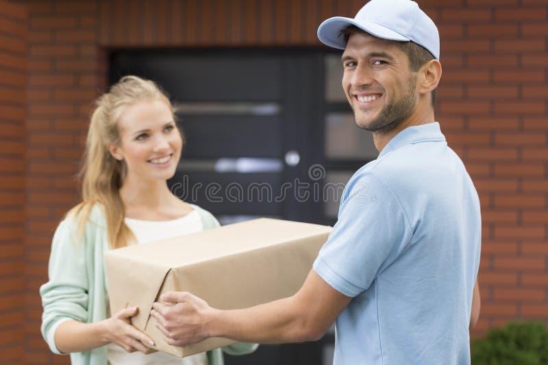 Messager heureux fournissant un paquet photographie stock
