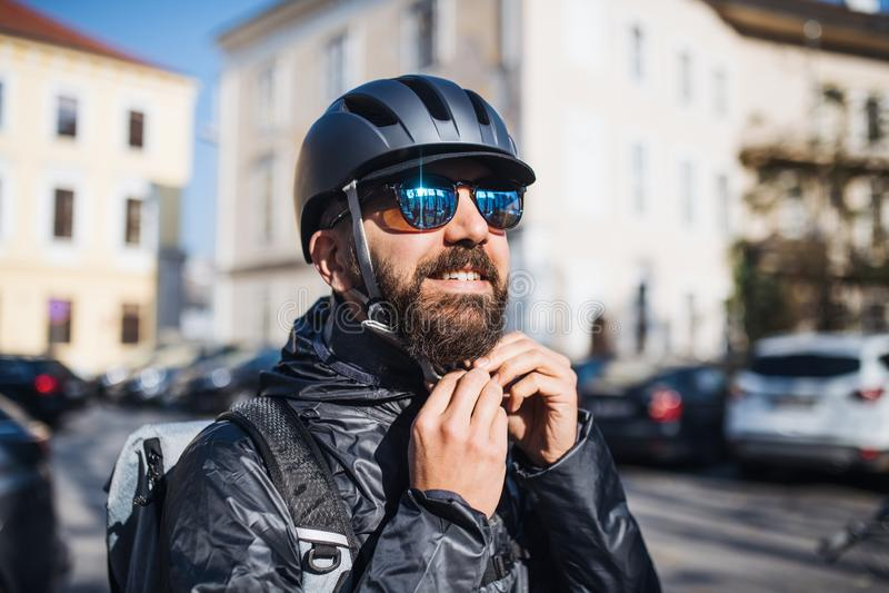 Messager masculin avec des lunettes de soleil fournissant des paquets dans la ville photo libre de droits