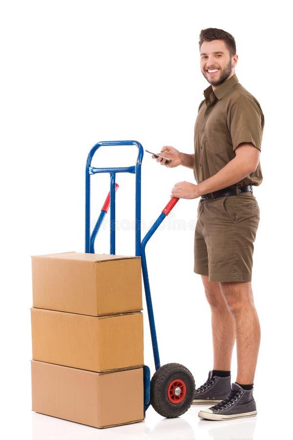 Messager Is Standing Close à un chariot de poussée, tenant le téléphone portable et le sourire photographie stock