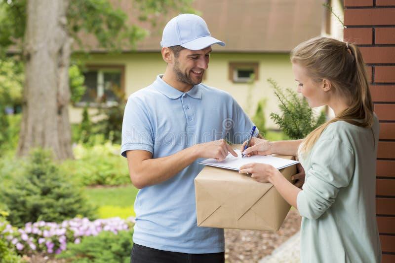 Messager tenant un colis et femme signant une forme de livraison photographie stock libre de droits