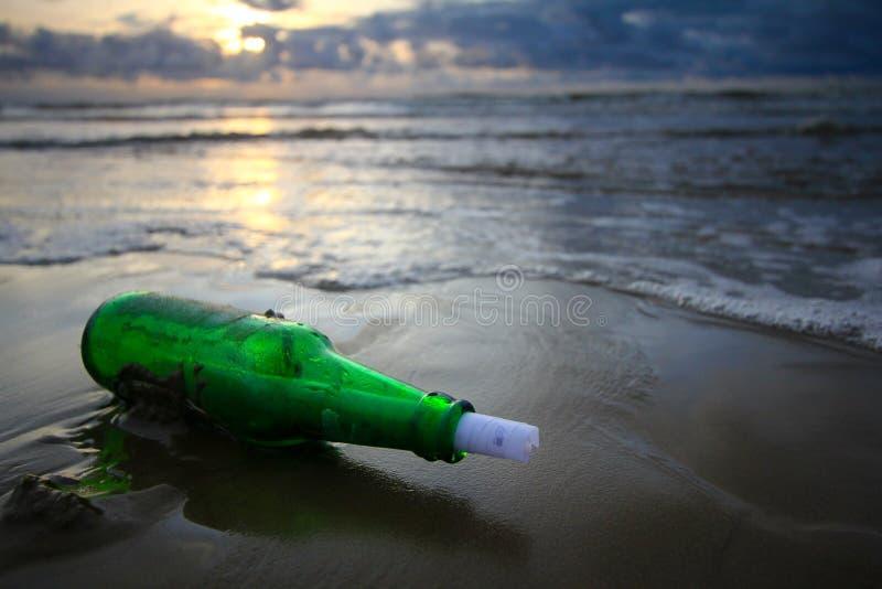 Messaggio in bottiglia al tramonto immagine stock