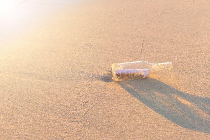 Messaggio in bottiglia sulla spiaggia con il backgro di industria della sfuocatura e di tramonto fotografie stock