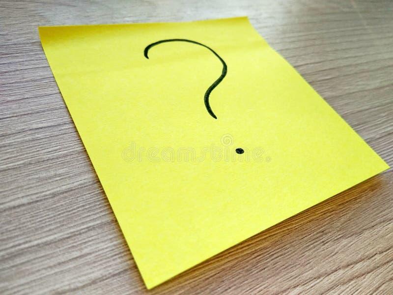 Messaggio del punto interrogativo sulla nota appiccicosa gialla su fondo di legno fotografia stock libera da diritti