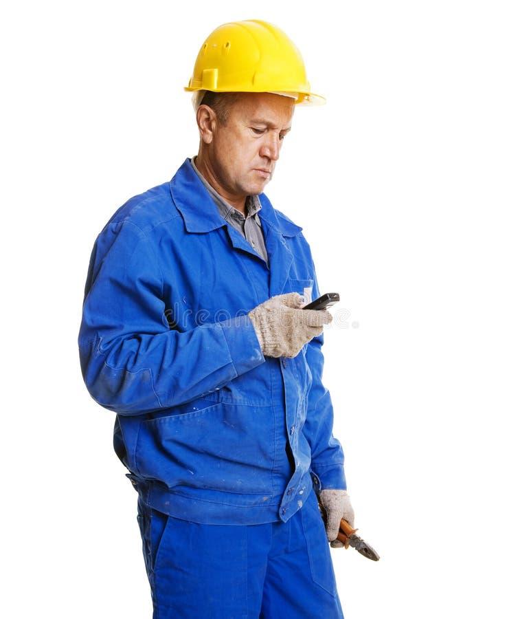 Messaggio della lettura dell'operaio in suo telefono mobile fotografia stock libera da diritti