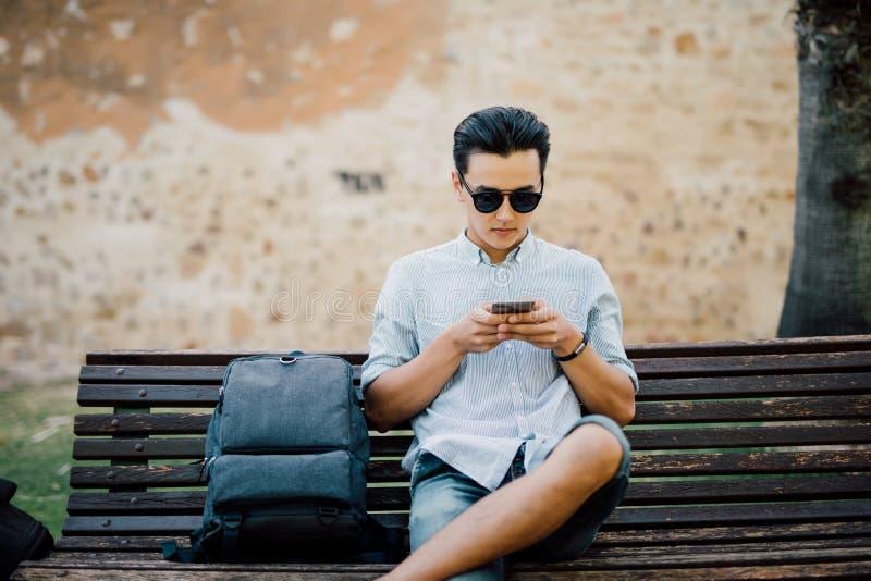 Messaggio di battitura a macchina dell'uomo asiatico bello sul suo Smart Phone che si siede sopra immagine stock