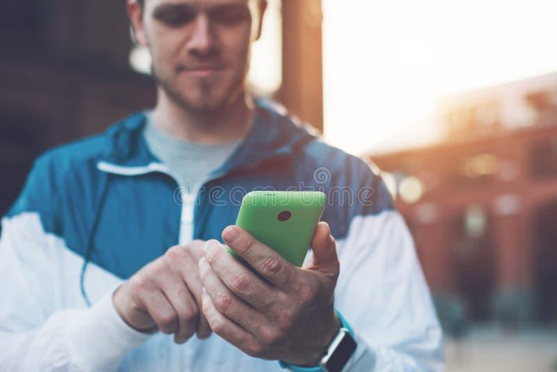 Messaggio di battitura a macchina sul suo telefono cellulare, tramonto dell'uomo bello sulla via immagine stock