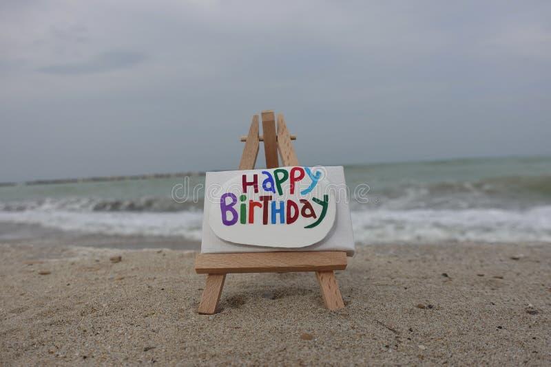 Messaggio di buon compleanno scolpito e dipinto su una pietra sopra un cavalletto con il fondo della spiaggia immagine stock libera da diritti