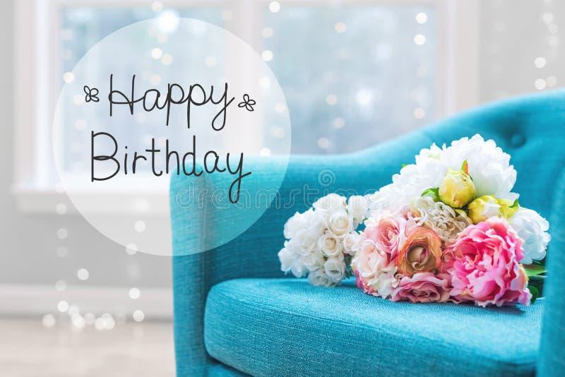 Messaggio di compleanno con i mazzi del fiore con la sedia immagini stock