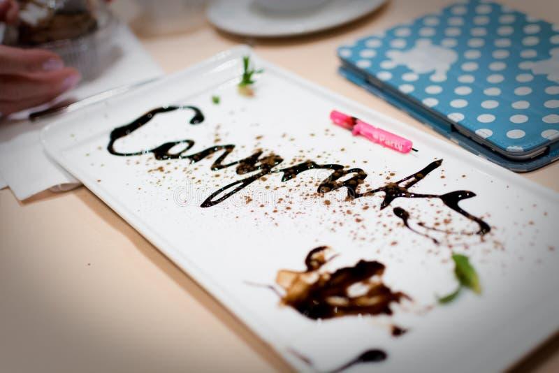Messaggio di congratulazioni scritto in cioccolato ad un partito di anniversario immagini stock