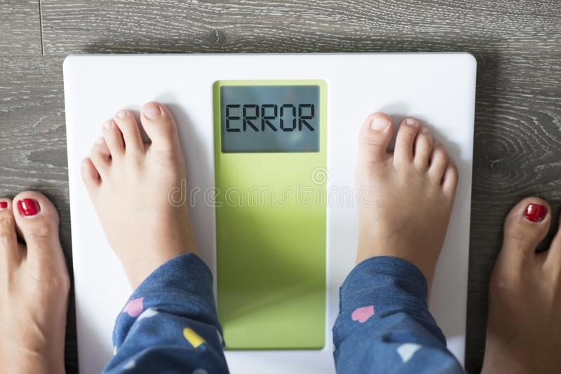 Messaggio di errore sull'esposizione della bilancia pesa-persone, ponderazione obesa del bambino nell'ambito del controllo dei pa immagini stock