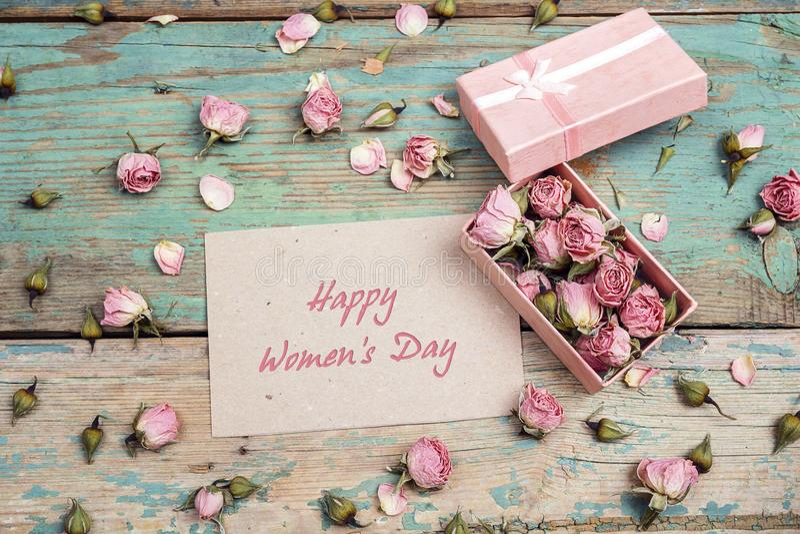 Messaggio di saluto di giorno del ` s delle donne con le piccole rose rosa in una scatola sopra immagine stock