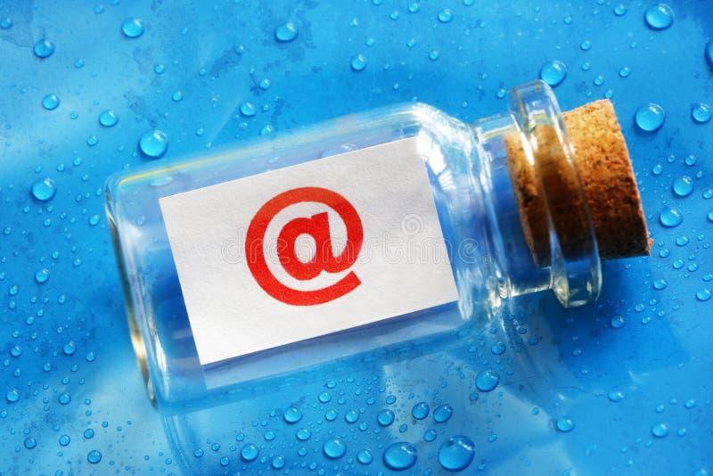 Messaggio di simbolo del email @ in una bottiglia fotografia stock libera da diritti