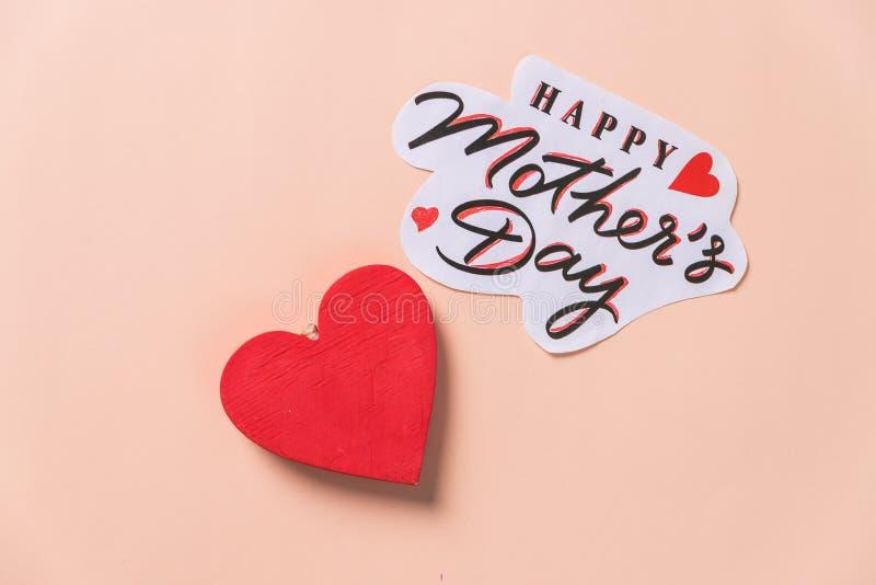 Messaggio felice di festa della Mamma con cuore di legno rosso su fondo pastello cartolina festiva Concetto di amore per il giorn fotografia stock