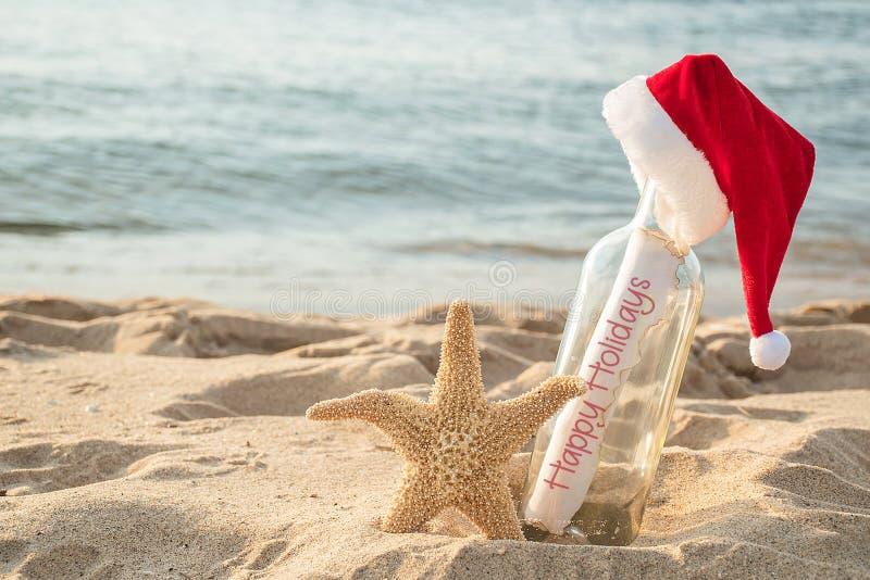 Messaggio felice di feste in una bottiglia con le stelle marine fotografia stock libera da diritti