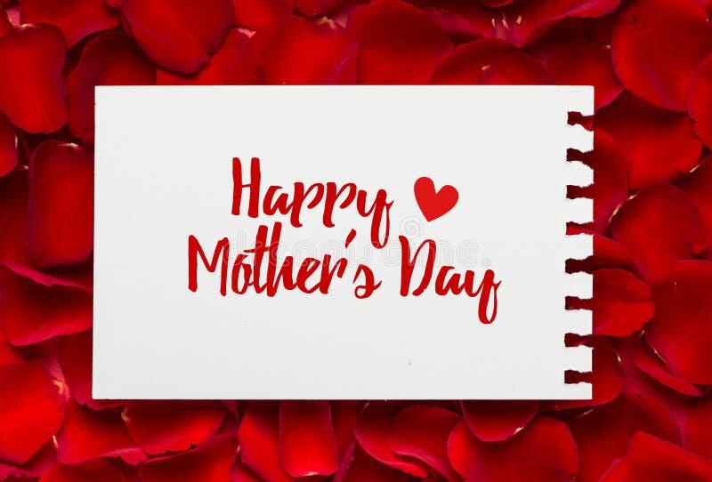 Messaggio felice di giorno di madri sul foglio di carta vuoto ed i petali rosa fotografie stock libere da diritti