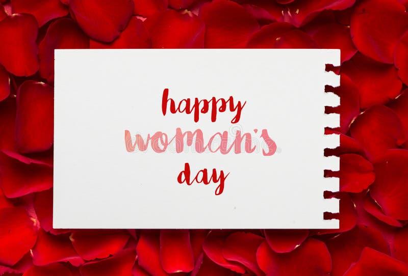 Messaggio felice di giorno di madri sul foglio di carta vuoto ed i petali rosa immagini stock libere da diritti