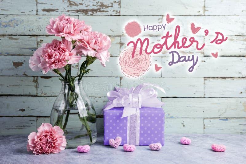 Messaggio felice di giorno di madri su fondo di legno e sul garofano rosa immagini stock