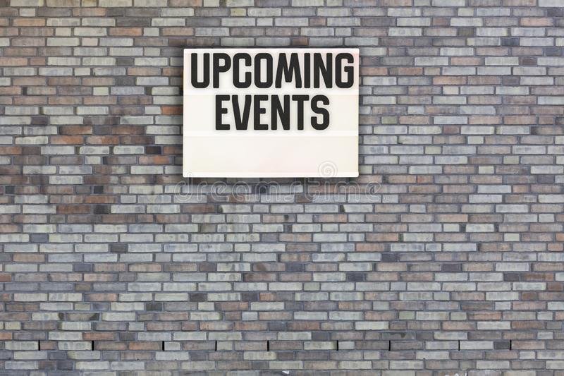 Messaggio imminente di eventi sul muro di mattoni con la scatola leggera fotografia stock