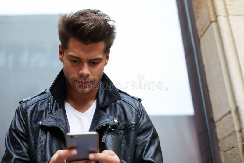 messaggio mandante un sms alla moda attraente dello studente maschio sul suo telefono cellulare fotografia stock