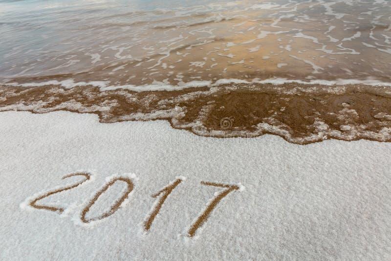 2017, messaggio scritto sulla sabbia ai precedenti della spiaggia della neve immagine stock libera da diritti