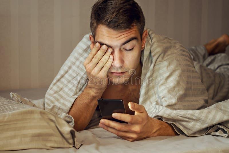 Messaggio sonnolento del giovane del ritratto del primo piano sullo Smart Phone a letto a casa, soffrendo dall'insonnia, problemi fotografie stock