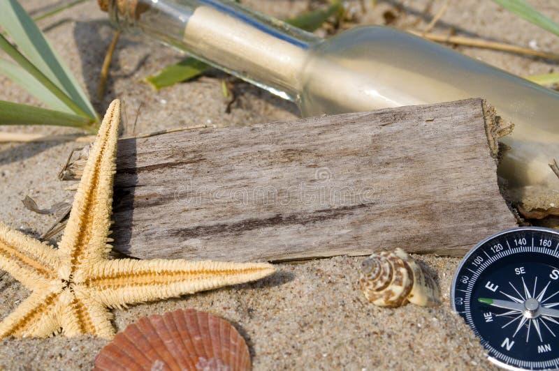 Messaggio in una bottiglia con legno, la lavagna e la decorazione marittima immagini stock libere da diritti