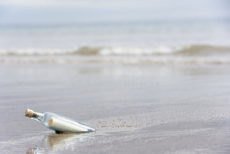 Messaggio in una bottiglia sepolta in sabbia fotografia stock libera da diritti