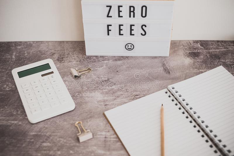 Messaggio zero delle tasse su lightbox circondato dal calcolatore delle monete fotografie stock